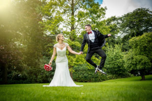 Groom jumps with Bride