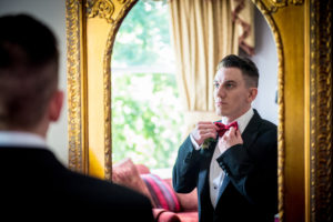 Groom Checking his Bow Tie in Mirror