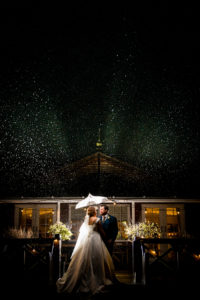 Bride and Groom in the Rain With Umbrella